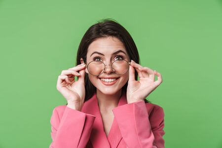 Image of happy young woman smiling and holding eyeglasses isolated over green background