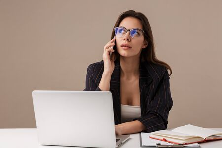 Photo of thinking businesswoman talking on cellphone while working with laptop isolated over grey background Banque d'images