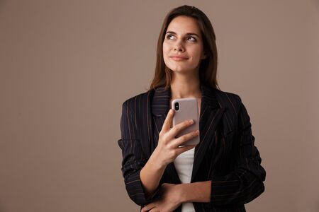 Photo of pleased businesswoman in formal suit smiling and using cellphone isolated over grey background