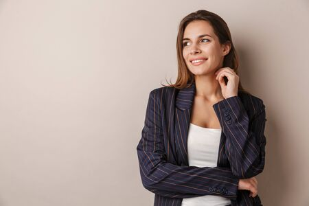 Photo of joyful businesswoman in formal suit smiling and looking aside isolated over white background