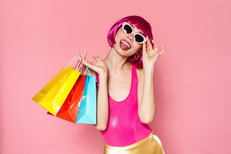 Image of amusing girl wearing wig sticking out her tongue and holding shopping bags isolated over pink background