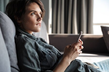 Image of nice young serious woman using mobile phone and thinking while sitting on sofa at living room Imagens