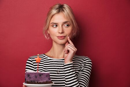 Image of nice thinking woman in striped sweatshirt holding cake with candle isolated over red background