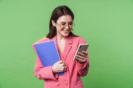 Portrait of a beautiful happy young elegant woman wearing pink jacket standing isolated over green background, using mobile phone, holding folder
