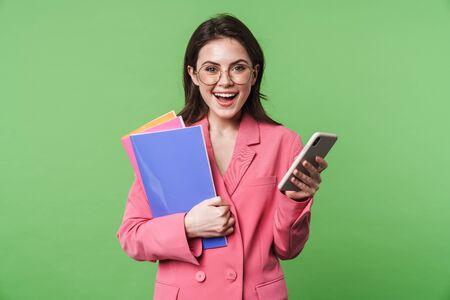 Portrait d'une belle jeune femme élégante et heureuse portant une veste rose isolée sur fond vert, utilisant un téléphone portable, tenant un dossier