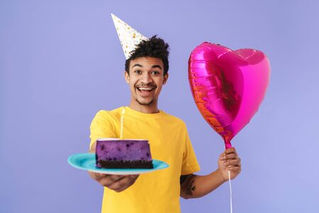 Photo of happy african american man in party cone holding cake and balloon isolated over purple background