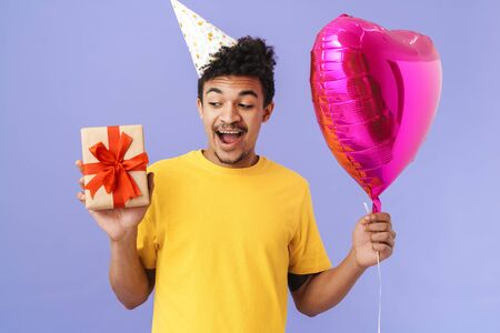 Photo of excited african american man in party cone holding gift box and balloon isolated over purple background 版權商用圖片