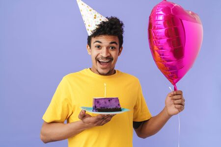 Photo of excited african american man in party cone holding cake and balloon isolated over purple background