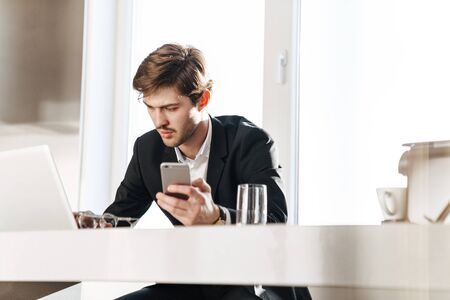 Photo of concentrated businessman wearing black suit working with laptop and cellphone at modern kitchen