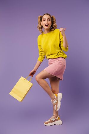Image of excited pretty woman with shopping bag pointing thumb backward isolated over purple background Stock Photo