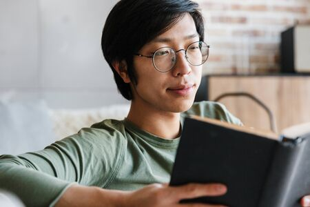 Image of handsome young asian man wearing eyeglasses reading book while sitting on couch in apartment