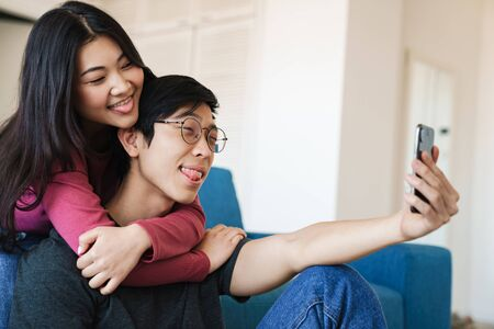 Photo of amusing asian couple showing their tongues and taking selfie on cellphone while sitting at room