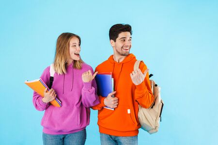 Portrait of a cheerful young couple of students wearing backpacks, carrying textbooks standing isolated over blue background, pointing away