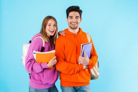Portrait of a cheerful young couple of students wearing backpacks, carrying textbooks standing isolated over blue background Archivio Fotografico