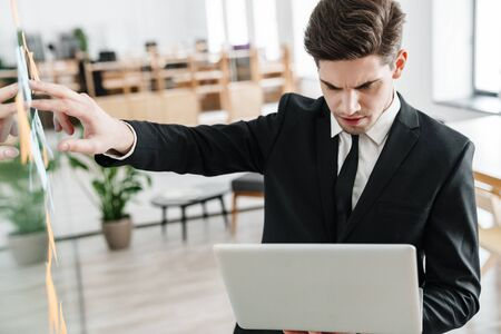 Image of concentrated young businessman wearing suit using laptop while working in office