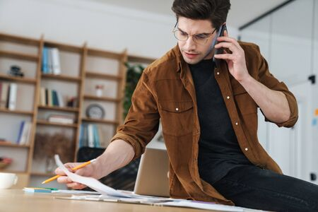 Image of handsome puzzled young man talking cellphone while working with documents in office