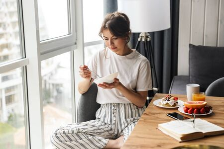 Photo of young caucasian cute woman having breakfast while sitting at table in cozy room