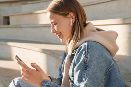 Beautiful smiling young blonde woman wearing denim jacket sitting on steps outdoors, listening to music with earphones and mobile phone