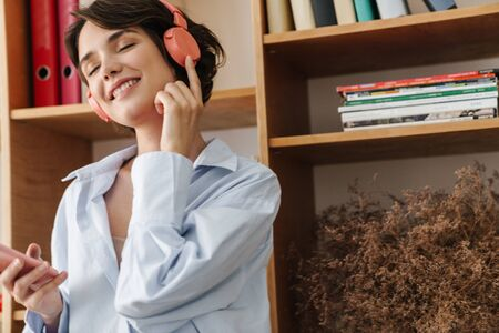 Smiling young woman entrepreneur listening to music with headphones and mobile phone in the office Фото со стока