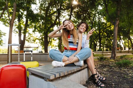 Photo of two delighted tourist women showing peace sign while sitting on bench with luggages in green park
