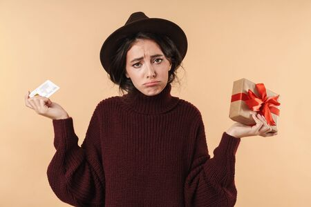 Image of displeased sad young brunette woman posing isolated over beige wall background holding credit card and present box.