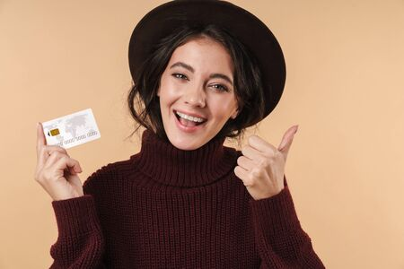 Image of smiling happy young brunette woman posing isolated over beige wall background holding credit card showing thumbs up.