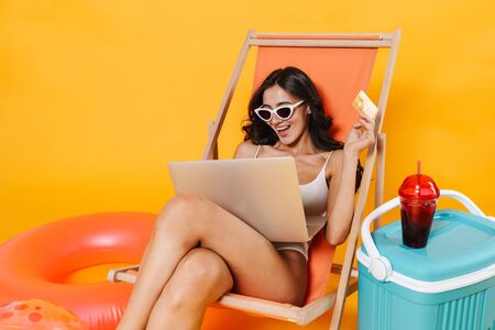 Image of happy woman using laptop and holding credit card while resting in chaise lounge isolated over yellow wall 스톡 콘텐츠