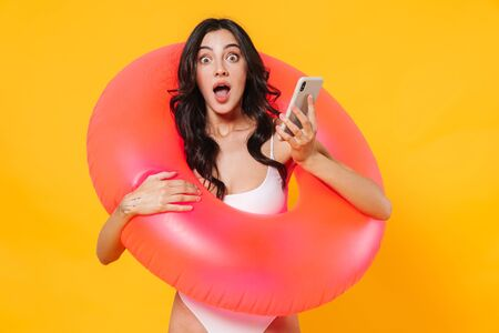 Image of surprised attractive young woman with rubber ring holding mobile phone isolated over yellow wall 版權商用圖片
