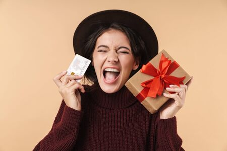 Image of screaming emotional young brunette woman posing isolated over beige wall background holding credit card and present box.