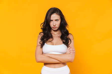 Image of displeased young woman in swimsuit posing on camera with arms crossed isolated over yellow wall