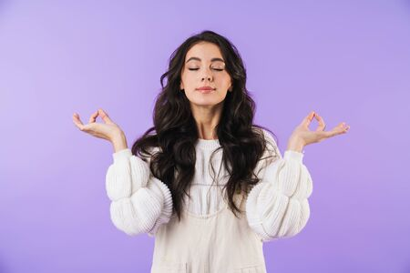 Photo of positive young brunette woman posing isolated over purple wall background meditate. 版權商用圖片