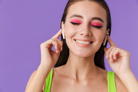 Photo of cute happy woman with bright makeup using earpods and smiling isolated over violet background