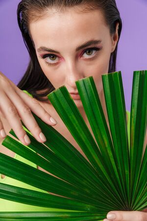 Photo closeup of nice brunette woman with bright makeup holding palm leaf isolated over violet background