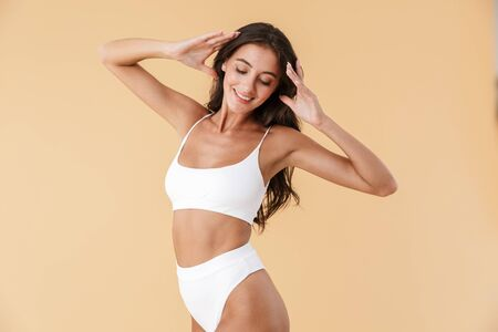 Attractive young slim girl posing in swimwear isolated over beige background, eyes closed