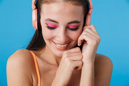 Photo closeup of alluring joyful woman using headphones and smiling isolated over blue background