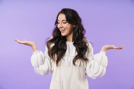 Photo of happy optimistic young brunette woman posing isolated over purple wall background showing copyspace.