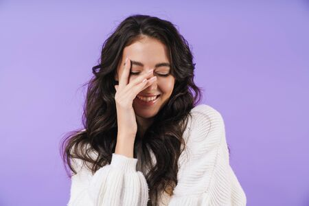 Image of cheery young brunette woman posing isolated over purple wall background covering face. 版權商用圖片