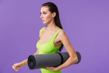 Photo of sporty serious woman with bright makeup holding yoga mat and looking forward isolated over violet background