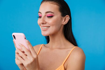 Photo closeup of alluring joyful woman using cellphone and smiling isolated over blue background 版權商用圖片