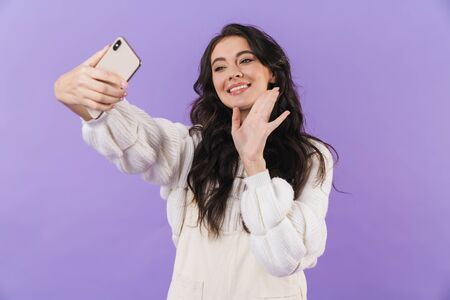 Image of cheerful pleased cute young brunette woman posing isolated over purple wall background take a selfie by mobile phone waving talking. 版權商用圖片