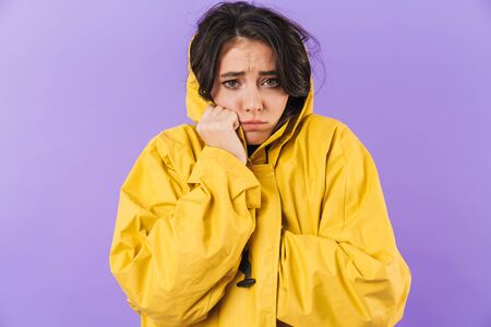 Photo of frozen cute brunette woman in yellow raincoat posing isolated over purple wall background.