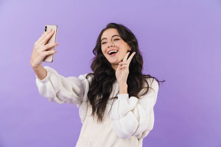 Image of positive pleased happy cute young brunette woman posing isolated over purple wall background take a selfie by mobile phone.