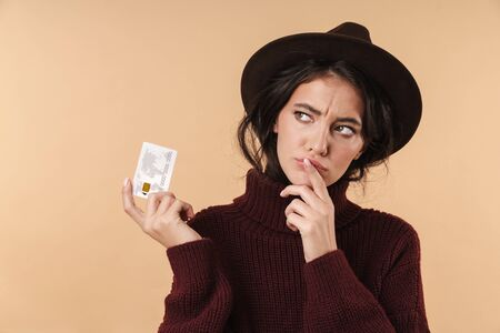 Image of thinking young brunette woman posing isolated over beige wall background holding credit card.