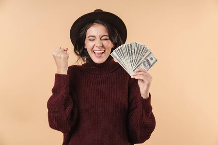 Photo of young screaming emotional brunette woman isolated over beige wall background holding money make winner gesture.