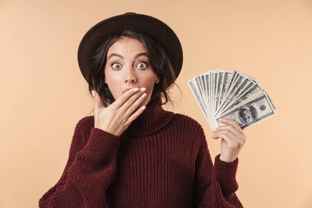 Photo of young shocked emotional brunette woman isolated over beige wall background holding money covering mouth. 版權商用圖片