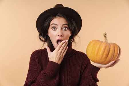 Photo of young shocked brunette woman isolated over beige wall background holding pumpkin. 版權商用圖片
