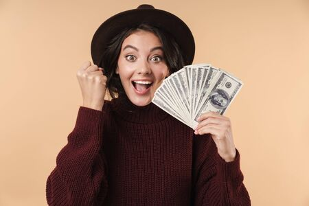 Photo of young happy brunette woman isolated over beige wall background holding money make winner gesture. 版權商用圖片
