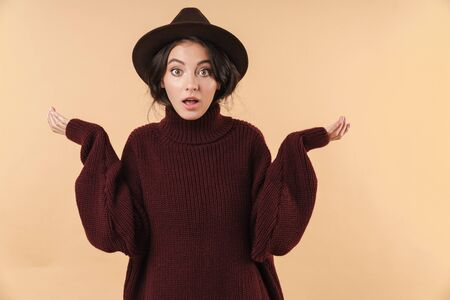 Image of shocked emotional young brunette woman posing isolated over beige wall background. 版權商用圖片