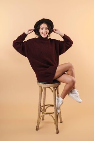 Image of happy cute young brunette woman posing isolated over beige wall background.