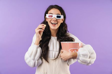 Photo of happy positive brunette woman posing isolated over purple wall background watch tv cinema in 3d glsases eat popcorn.